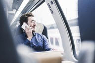 Smiling businessman in train on cell phone - UUF12629