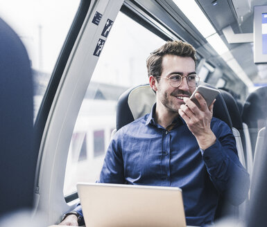 Smiling businessman in train using cell phone - UUF12632