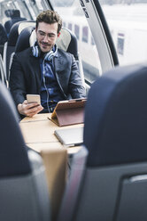 Businessman in train with cell phone, headphones and tablet - UUF12635