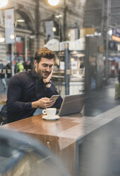 Young businessman in a cafe at train station with cell phone and laptop - UUF12641