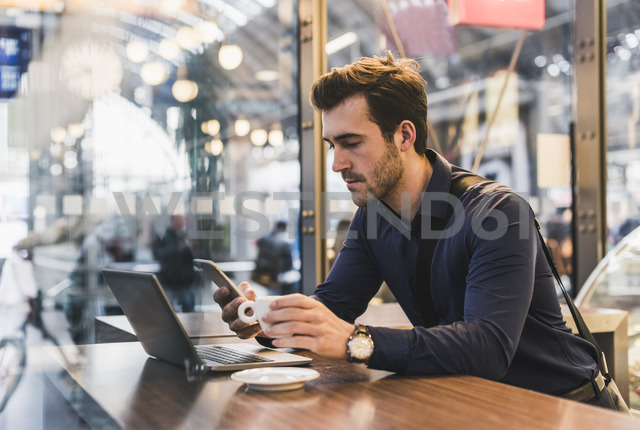 Young businessman in a cafe at train station with cell phone and laptop - UUF12644 - Uwe Umstätter/Westend61