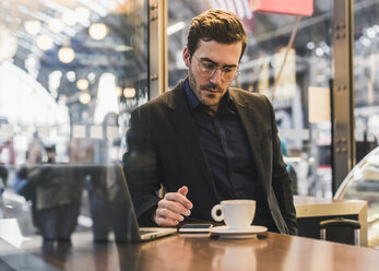 Young businessman in a cafe at train station with cup of coffee, laptop and cell phone - UUF12647