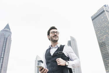 Germany, Frankfurt, confident young businessman with cell phone in the city - UUF12650