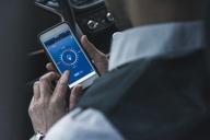 Man in car adjusting smart home device via smartphone - UUF12653