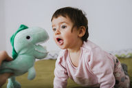 Baby girl with open mouth crawling on bed - GEMF01872