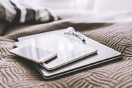 Stack of three mobile devices on bed - GIOF03859