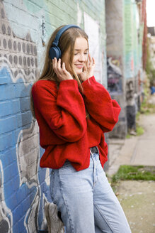 Germany, Berlin, smiling young woman listening music with headphones - OJF00236