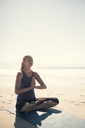 Young woman exercising yoga at a beach - ABAF02200