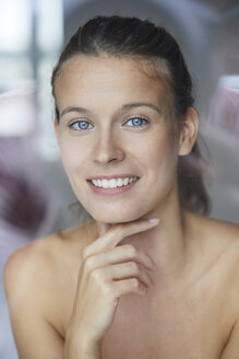 Portrait of smiling young woman behind windowpane - PNEF00401