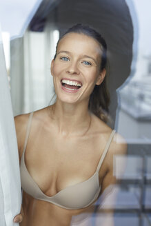 Portrait of laughing young woman behind windowpane wearing bra - PNEF00407