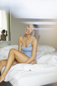 Portrait of happy young woman sitting on bed - PNEF00410