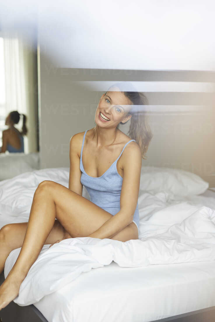 Portrait of happy young woman sitting on bed - PNEF00410 - Philipp Nemenz/Westend61