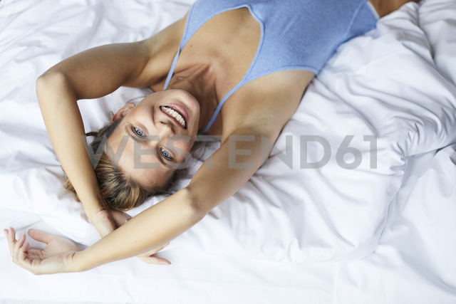 Portrait of happy young woman lying in bed - PNEF00413