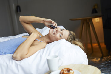 Happy young woman lying in bed talking on cell phone - PNEF00416