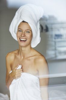 Portrait of happy young woman behind windowpane wrapped in towels - PNEF00419