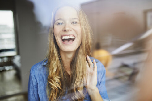 Portrait of laughing young woman behind windowpane - PNEF00422