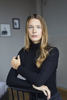 Portrait of young woman wearing black turtleneck sitting on chair - PNEF00425