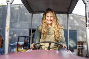 Portrait of smiling woman driving a tractor - PESF00898