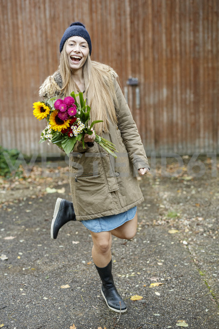 Portrait of happy young woman holding bunch of flowers on yard - PESF00901