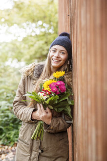Portrait of smiling young woman holding bunch of flowers outdoors - PESF00904
