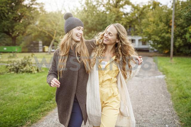 Two happy women walking in rural landscape - PESF00910