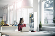 Smiling woman sitting at table with laptop in a loft looking out of window - MOEF00711