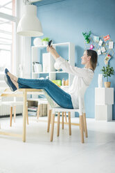 Smiling woman with feet up taking selfie in a loft - MOEF00714