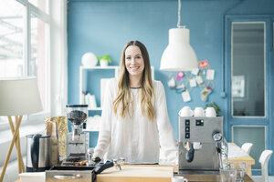 Portrait of happy young businesswoman in kitchen of a loft - MOEF00717