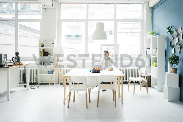 Smiling woman working on laptop in a loft - MOEF00720
