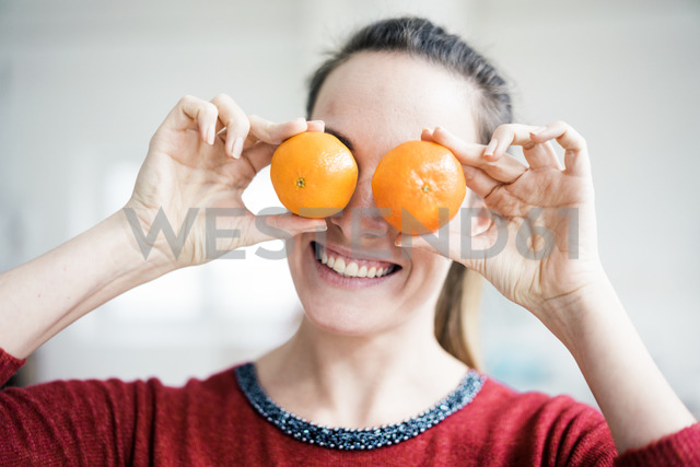 Laughing woman covering her eyes with oranges - MOEF00732