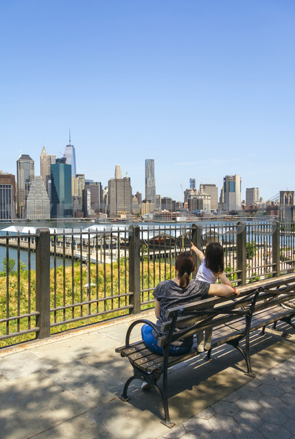 USA, New York, Brooklyn, Back view of woman and young girl sitting on bench while looking the skyline of Manhattan from Brooklyn - DAPF00868 - David Pereiras/Westend61
