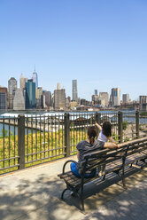 USA, New York, Brooklyn, Back view of woman and young girl sitting on bench while looking the skyline of Manhattan from Brooklyn - DAPF00868