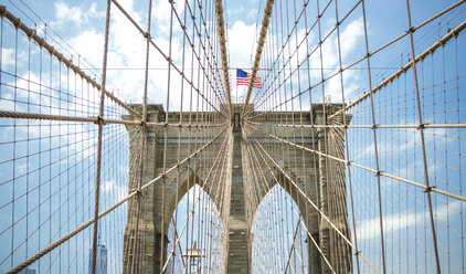 USA, New York, Brooklyn, Close up of Brooklyn Bridge metal cables and arches with american flag on the top - DAPF00874