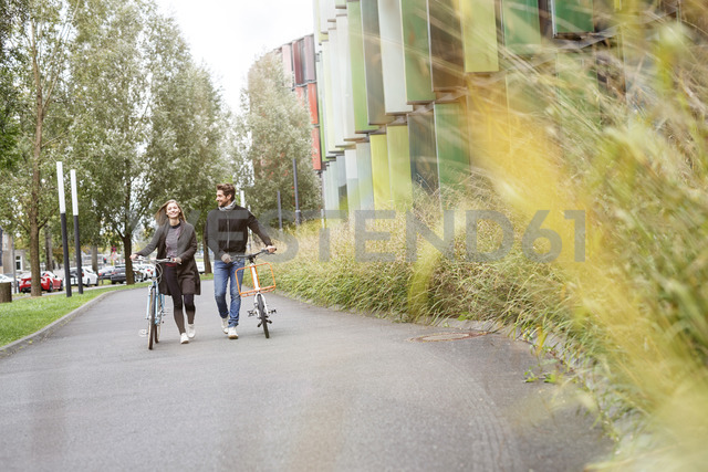Smiling couple walking with bicycles on a lane - PESF00913 - Peter Scholl/Westend61
