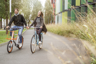Happy couple riding bicycle hand in hand on a lane - PESF00916