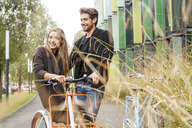 Smiling couple with bicycles on a lane - PESF00919