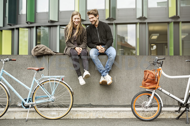 Happy couple with bicycles sitting on a wall - PESF00922 - Peter Scholl/Westend61