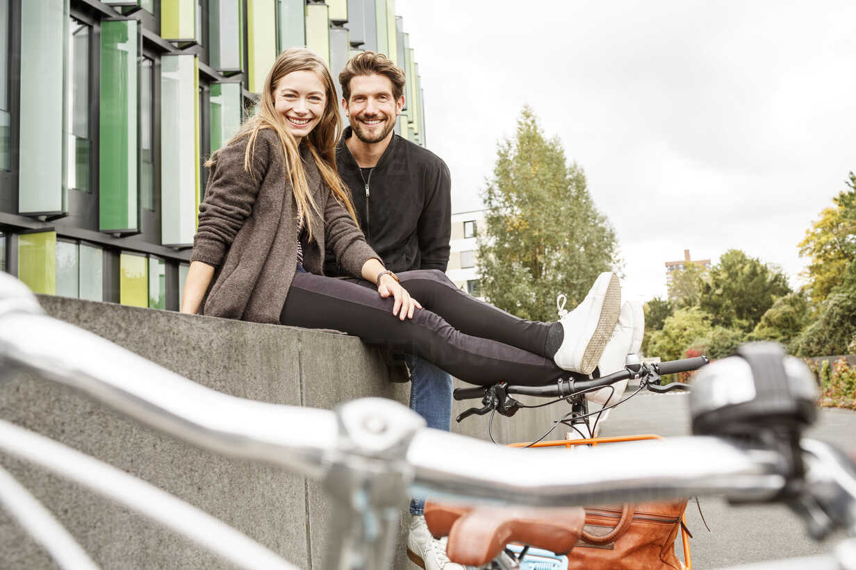 Portrait of smiling couple with bicycles sitting on a wall - PESF00925 - Peter Scholl/Westend61