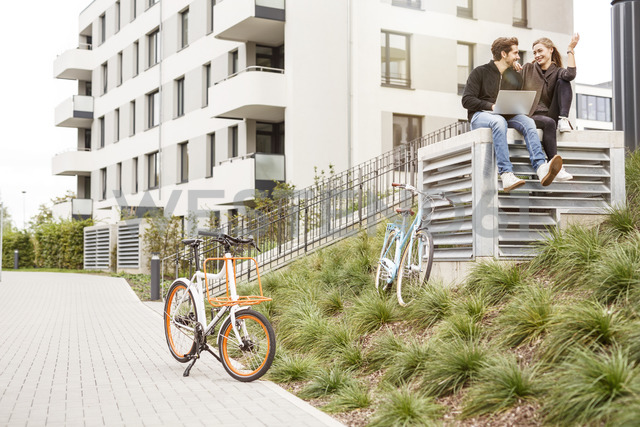 Happy couple with bicycles and laptop in urban surrounding - PESF00931 - Peter Scholl/Westend61