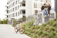 Happy couple with bicycles and laptop in urban surrounding - PESF00931