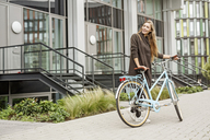 Smiling woman with bicycle standing in front of a building - PESF00937
