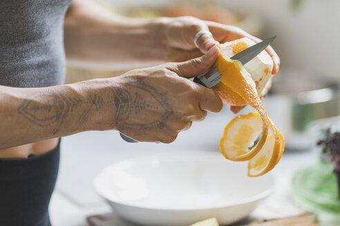 Woman preeling an orange - ASCF00784