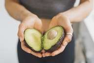 Hands of woman holding halved avocado - ASCF00796