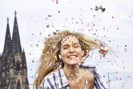 Germany, Cologne, portrait of happy blond woman in between shower of confetti - FMKF04742