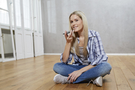 Portrait of smiling blond woman sitting on the floor using cell phone - FMKF04745