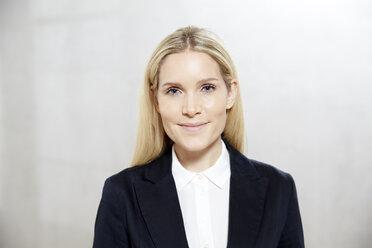 Portrait of smiling blond businesswoman - FMKF04748