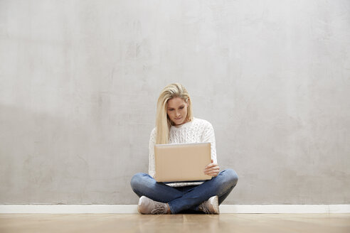 Blond woman sitting on the floor in front of grey wall using laptop - FMKF04751