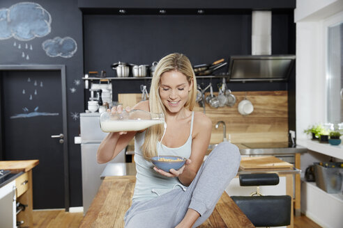 Blond woman sitting on kitchen table pouring milk on cereals - FMKF04754