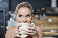 Portrait of smiling blond woman in the kitchen holding coffee mug - FMKF04757