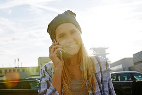 Portrait of happy blond woman on the phone at backlight - FMKF04760